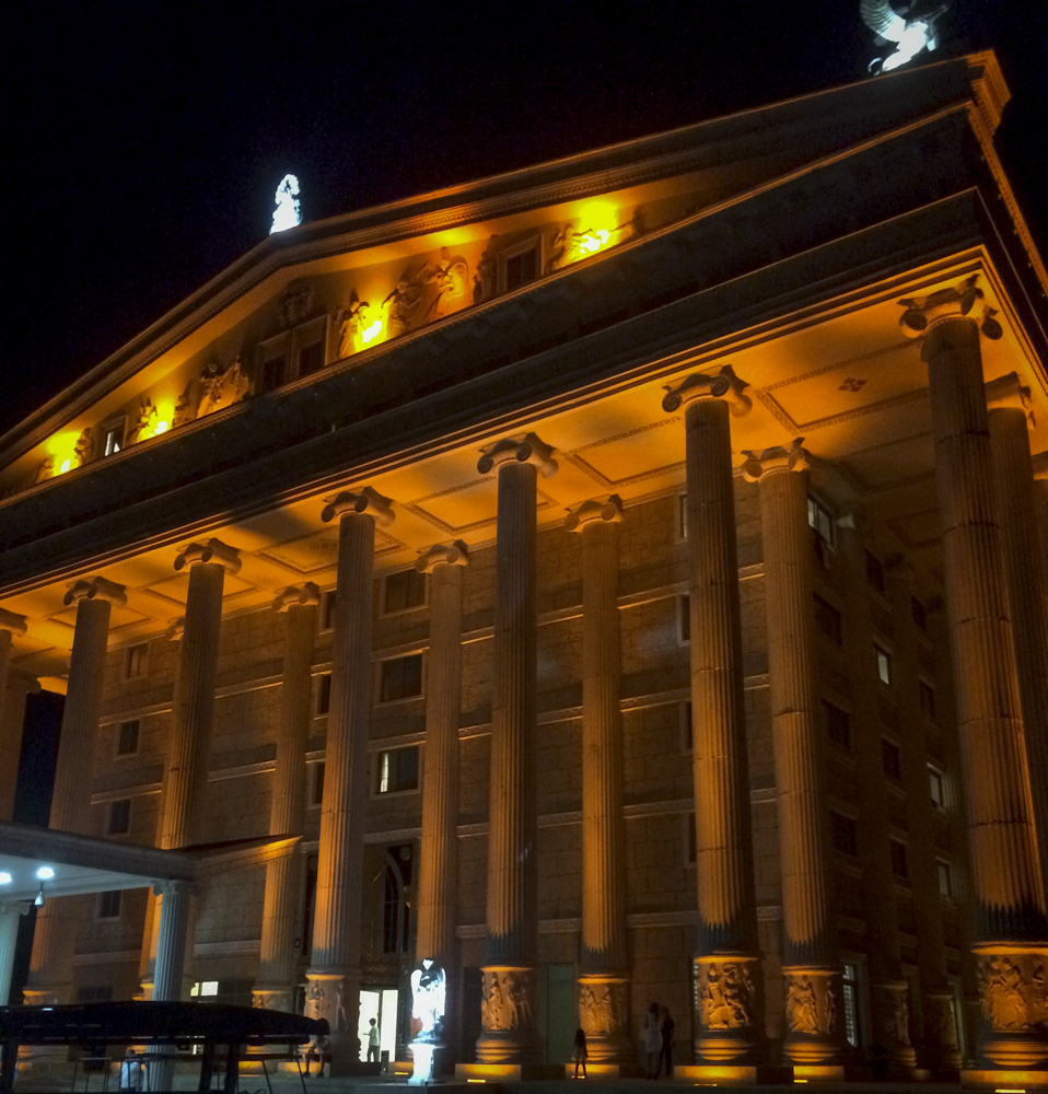 Image shows the facade of a faux Greek temple at night, lit by warm lights.